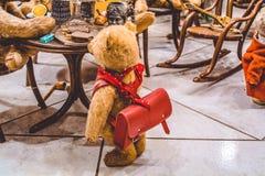 Nallebrunbjörnar sitter på en tabell och äter glass, och nära dem ungen med en ryggsäck Utställning av leksaker meddelande arkivfoto