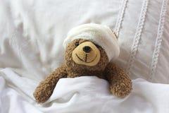 Nallen i björnsäng med förbinder på huvudet Arkivfoto