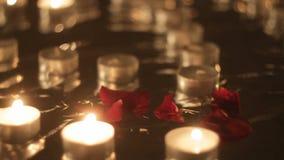 Nam bloemblaadjes naast het branden van kaarsen, close-up, panorama toe stock footage