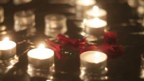 Nam bloemblaadjes naast het branden van kaarsen, close-up, panorama toe stock videobeelden
