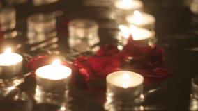 Nam bloemblaadjes naast het branden van kaarsen, close-up toe stock videobeelden