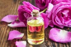 Nam etherische olie met roze rozen en bloemblaadjes op houten raad toe stock foto