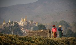 Women walking on the shore of Inle lake at the Nampan Market with a pagoda in the background, Inle Lake, Shan State, Myanmar Stock Images