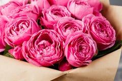 Nam pioen Misty Bubbles toe Boeketbloemen van roze rozen in glasvaas op donkere grijze rustieke houten achtergrond Sjofele elegan Royalty-vrije Stock Fotografie