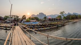Nam Song River, Laos. Tourists crossing wooden foot bridge over the Nam Song River. Sun setting over impressive limestone mountains in the background. Vang Vieng stock photos