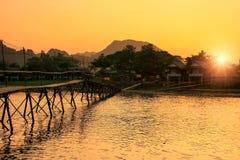 Nam Song River med träbron på solnedgången i Vang Vieng, Laos royaltyfri fotografi