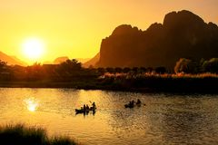 Nam Song River at sunset with silhouetted rock formations and kayakers in Vang Vieng, Laos. Vang Vieng is a popular destination for adventure tourism in a royalty free stock photography