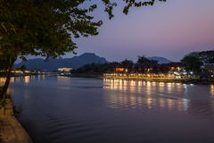 Nam Song River in Vang Vieng at dusk. Lit waterfront restaurant, bungalows and buildings and their reflections on the Nam Song Rvier in Vang Vieng, Vientiane royalty free stock photos