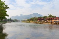 Nam Song River in Vang Vieng, Laos. Nam Song River and waterfront restaurant, bungalows and buildings in Vang Vieng, Vientiane Province, Laos, on a sunny day royalty free stock image