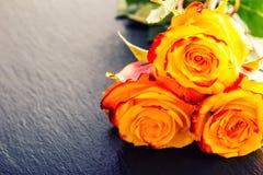Nam toe Oranje nam toe Geel nam toe Verscheidene oranje rozen op Granietachtergrond Royalty-vrije Stock Foto's