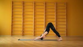 Namaskar Surya Vrouw in zwarte bodysuit die yogapraktijk in gele studio op tredenachtergrond doen Gezondheid, levensstijl stock video