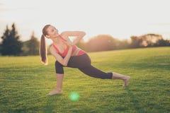 Namaste! Молодая жизнерадостная женщина делает сложную тренировку йоги вне Стоковые Изображения