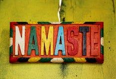 Namaste. Colorful sign NAMASTE – the Sanskrit salutation - on old rustic wall Stock Images