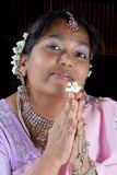 Namaste with a flower. Friendly Indian woman greeting the Namaste greeting with a flower Stock Photography
