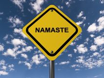 Namaste sign. An yellow traffic sign against the blue skies with the Hindu greeting 'Namaste Stock Photography