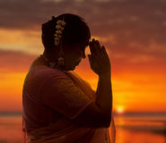Namaste at sunset. Indian lady in saree doing the namaste greeting at sunset stock photos
