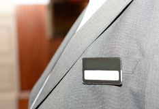 Name badge. A close up of a man wearing a suit with a blank name badge on the chest stock images