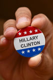 The name of Hillary Clinton in a campaign button. BARCELONA, SPAIN - AUGUST 26: Man showing a campaign button with the name of Hillary Clinton and the colors and Stock Image