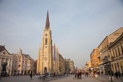 The Name of Mary Church, or Novi Sad catholic cathedral on a sunny afternoon with a crowd walking on Trg Slobode Square. stock images