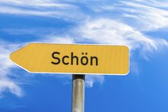 Name of village schoen - english beauty - on a street sign. Name of village schoen - english beauty - on a yellow street sign stock image