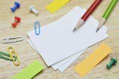 Namecard, lápis, grampo e notas pegajosas na tabela Foto de Stock