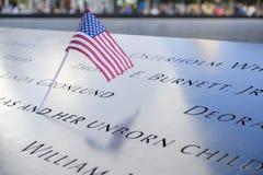 Namen und eine USA-Flagge an den 9/11 Denkmälern stockfotografie