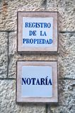 Nameplate office of a notary. Nameplate of an office of notary. In spanish language; text at upper sign means:registration of ownership Stock Photos