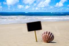Nameplate with seashell on the sandy beach Stock Photos