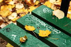 Names on park bench. Hearts and names carved or written in the wood of a green park bench in fall stock images