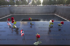 Names and red roses on ground zero monument Stock Photos