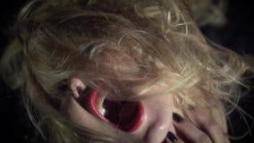 Namiętna czarownica z czerwonymi wargami krzyczy w zmroku, zwolnione tempo zdjęcie wideo
