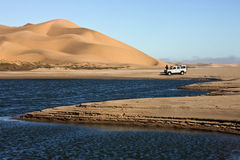 Namib Desert - Namibia. Adventure tourists with vehicle in the Namib Desert in Namib-Nuakluft National Park near Sandwich Bay on the coast of Namibia royalty free stock photos