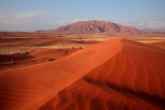 Namib Rand Nature Reserve – Sand Dunes of Wolwedans. Glowing red sand dune with Losberg in background. Picture was taken at Wolwedans, Namib Rand Nature stock image