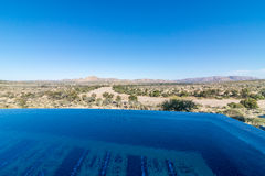 Namiba landscape with infinity pool. Namibian landscape of mountains in background against a blue sky and an infinity swimming pool in the foreground.  Game Stock Photos