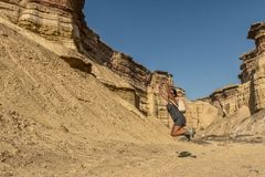 NAMIBE/ANGOLA 03NOV2018 - Young girl jumping in the middle of canyons of the Namibe Desert. Angola. Africa. Africa royalty free stock image