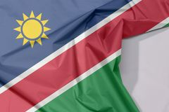 Namibia fabric flag crepe and crease with white space. Namibia fabric flag crepe and crease with white space, a white-edged red diagonal band and triangle is stock image