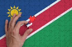 Namibia flag is depicted on a puzzle, which the man`s hand completes to fold.  royalty free illustration