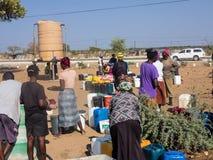 NAMIBIA Kavango, OKTOBER 15: Kvinnor i det väntande på vattnet för by Kavango var regionen med den högsta armodleven Royaltyfri Bild