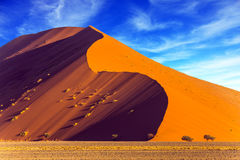 Namibia, South Africa. The concept of extreme and exotic tourism. Sharp border of light and shadow over the crest of the dune. The Namib-Naukluft at sunset Stock Images