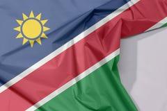 Namibia tkaniny flaga zagniecenie z biel przestrzenią i krepa obraz stock