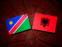 Namibian flag with Albanian flag on a tree stump isolated. Namibian flag with Albanian flag on a tree stump Stock Photos