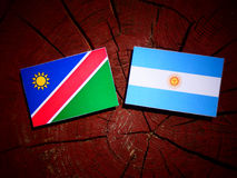 Namibian flag with Argentinian flag on a tree stump isolated. Namibian flag with Argentinian flag on a tree stump Royalty Free Stock Photography