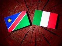 Namibian flag with Italian flag on a tree stump isolated. Namibian flag with Italian flag on a tree stump Stock Photos