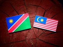 Namibian flag with Malaysian flag on a tree stump isolated. Namibian flag with Malaysian flag on a tree stump Stock Photos