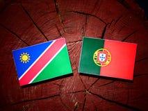 Namibian flag with Portuguese flag on a tree stump isolated. Namibian flag with Portuguese flag on a tree stump Royalty Free Stock Photos