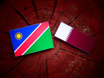 Namibian flag with Qatari flag on a tree stump isolated. Namibian flag with Qatari flag on a tree stump Stock Photography