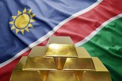 Namibian gold reserves. Shining golden bullions on the namibian flag background Royalty Free Stock Photography