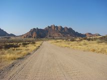 Namibian gravel road with mountains in background Royalty Free Stock Images