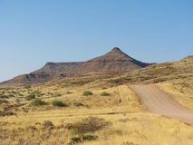 Namibian gravel road with mountains in background Royalty Free Stock Image