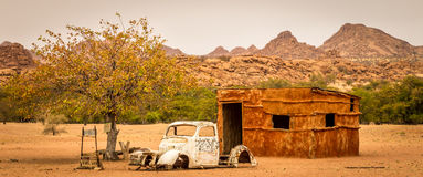 A namibian hut and a broken car - Poverty in Africa. In front of mountains in the very dry desert Royalty Free Stock Image